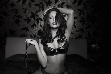 Sexy woman holding handcuffs black and white