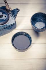 Black teapot, bowl of green tea on white wooden table
