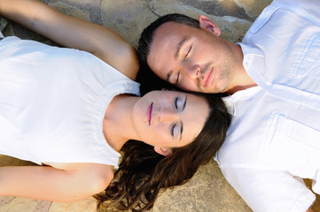Young couple lying on a stone floor with eyes closed