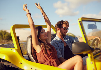 Cheerful young couple enjoying road trip