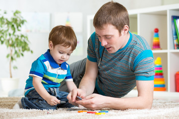 dad and kid playing toys at home