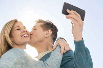 Man Kissing Woman While Taking Self Portrait On Cell Phone
