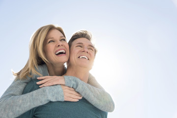 Man Giving Piggyback Ride To Woman Against Clear Sky