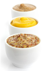 Three kinds of mustard in a line in perspective. Isolated.