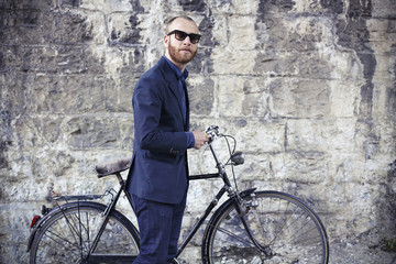 Portrait of beautiful adult man with a vintage bike