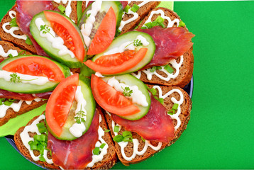 Sandwich with smoked meat and vegetables on green background