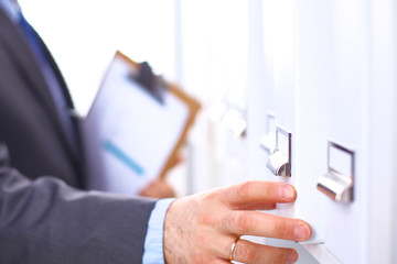 Man's hand holding big folder from the shelves with office files