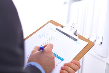 Man's hand holding folder from the shelves with office files