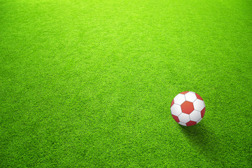 Artificial green soccerfield with red ball