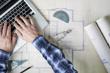an architect working with blueprints and a laptop computer