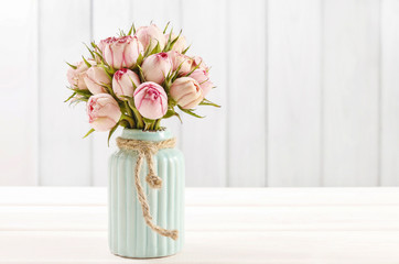 Bouquet of pink roses in turquoise ceramic vase
