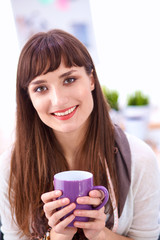 Modern young fashion designer with cup at studio
