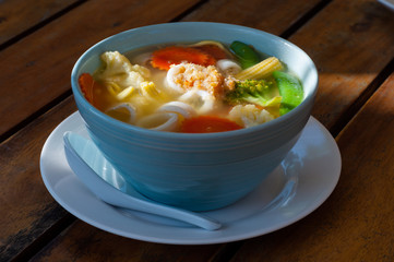 Vegetable soup with noodles on a wooden table