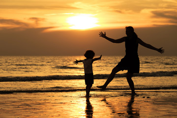 Mother and son playing on the beach at the sunset time.