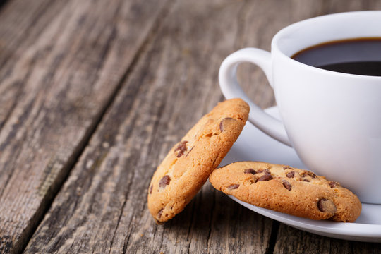 Cup of coffee with cookies on a wooden table.