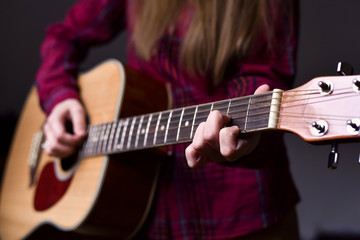woman's hands playing acoustic guitar, close up, finger position