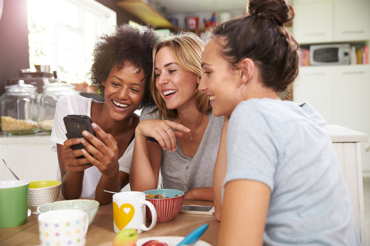 Female Friends Eating Breakfast Whilst Checking Mobile Phone