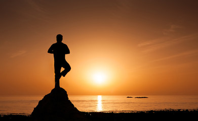 Man performing yoga on the beach during sunrise