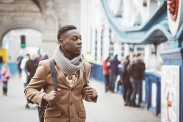 Young black man in London walking  on Tower Bridge
