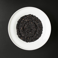 Black rice heap in ceramic dish top view close up isolated on