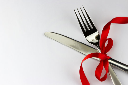 Top view of silver fork and knife decorated red ribbon with bow