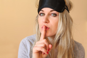 Young women with sleeping mask on, finger on lips