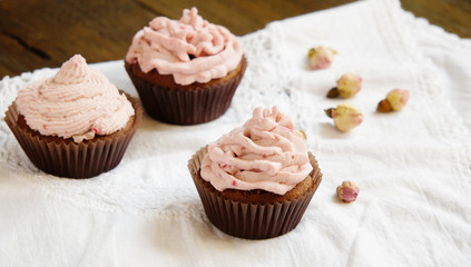 Cupcakes with cream cheese cream with raspberry and dry roses