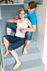 Couple at home sitting at stairs and relaxing with a glass of red wine