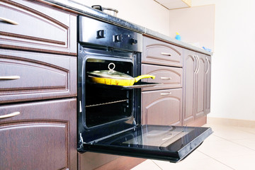 Modern kitchen. Open oven and yellow frying pan