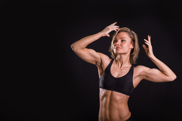 Sexy athletic blonde posing on a black background. Muscular girl