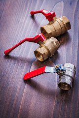 three plumbers fixtures with red handles on vintage wooden board
