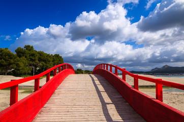 Red wooden footbridge on Alcudia beach, Majorca island, Spain