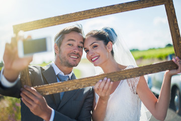A lovely couple is taking selfies for their wedding.