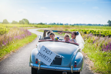 A newlywed couple is driving a retro car with their kids