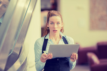 Shocked woman with computer laptop standing in her office
