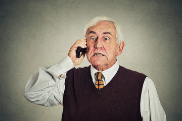 Angry senior man talking on mobile phone gray background