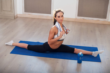 Young dark-haired athletic sporty slim woman doing yoga exercise