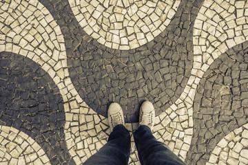 Sneakers shoes walking on Copacabana sidewalk top view