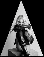 Fashion portrait of blond woman in leather jacket and boots. Vog