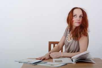 red-haired girl sitting at the table with Newspapers