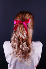 Female hairstyle with color ribbon on dark background