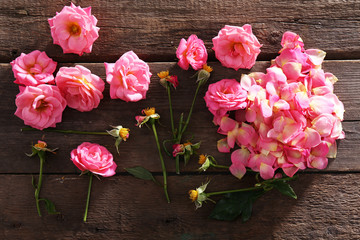 Beautiful pink roses on wooden table, top view