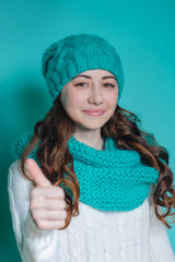 Portrait of a pretty woman in a knitted hat and scarf in studio