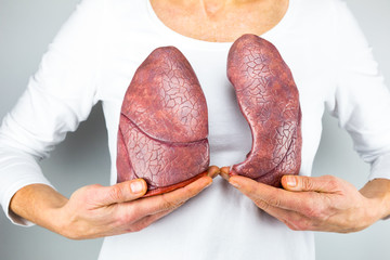 Woman showing two lungs in front of chest