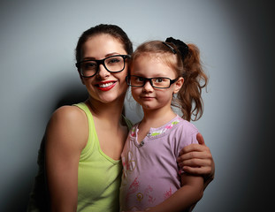Happy mother and cute girl in fashion black glasses looking