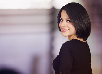 Beautiful latin woman looking back and smiling