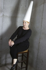 Woman in Dunce Cap sitting in Corner