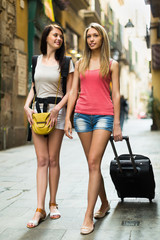 Two happy women with luggage