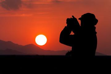 silhouette of beautiful women photographing at sunrise range