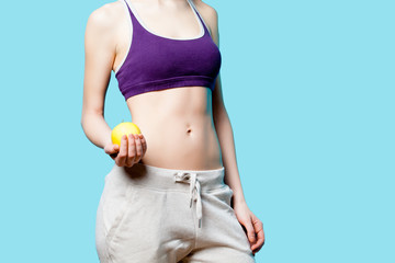 Woman showing her abs with apple after weight loss